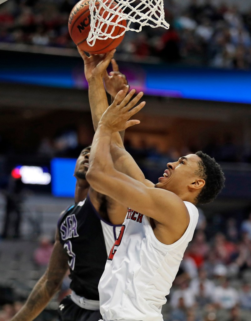 Texas Tech's Zhaire Smith (2) tries to lay up the ball as he is blocked by Stephen F. Austin's Leon Gilmore (3) during an NCAA college basketball tournament first-round game Thursday, March 15, 2018, at American Airlines Center in Dallas, Texas. [Brad Tollefson/A-J Media]