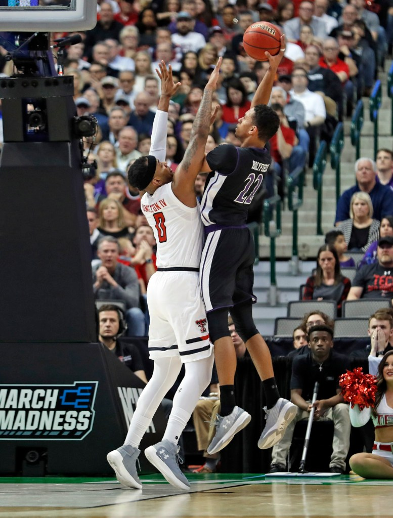 Texas Tech's Tommy Hamilton (0) tries to block a shot by Stephen F. Austin's TJ Holyfield (22) during an NCAA college basketball tournament first-round game Thursday, March 15, 2018, at American Airlines Center in Dallas, Texas. [Brad Tollefson/A-J Media]