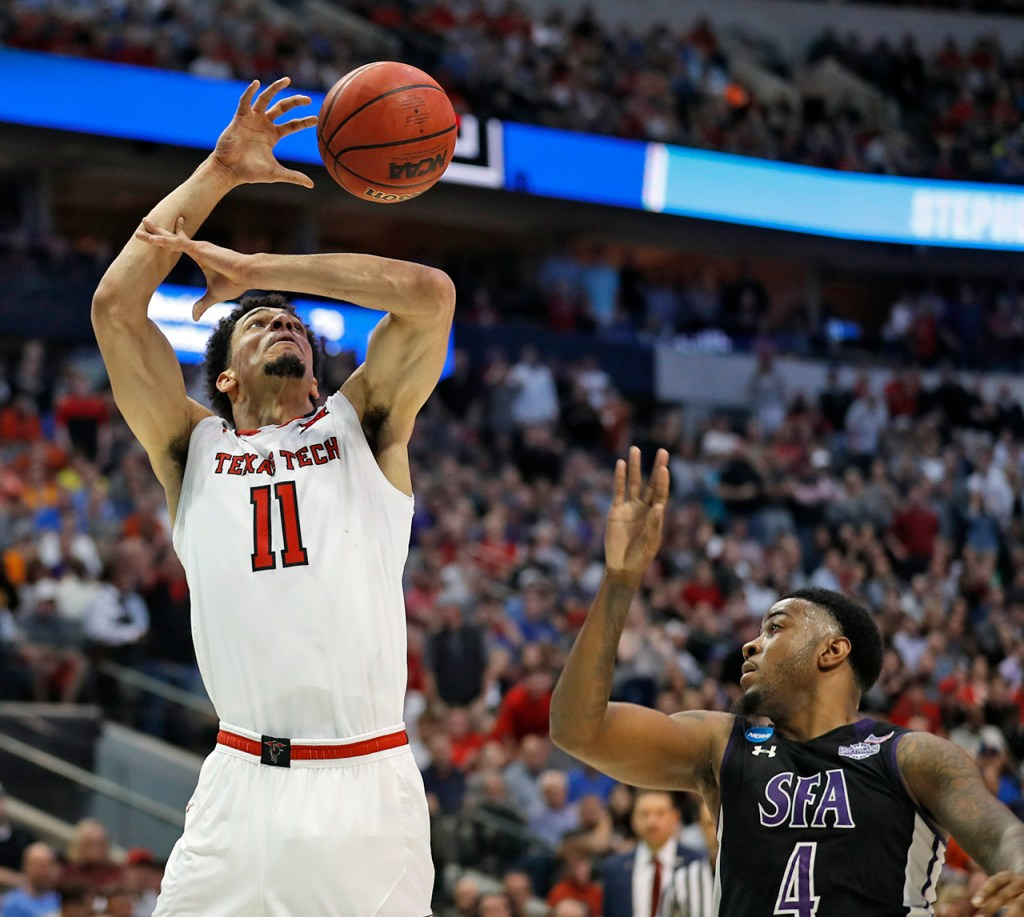Texas Tech's Zach Smith (11) loses control of the ball after being fouled by Stephen F. Austin's Ty Charles (4) during an NCAA college basketball tournament first-round game Thursday, March 15, 2018, at American Airlines Center in Dallas, Texas. [Brad Tollefson/A-J Media]
