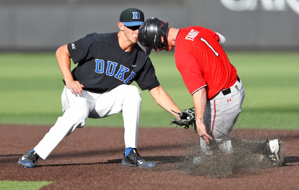 Duke's Zack Kone (2) tags out Texas Tech's Cody Farhat (1) as he slides into second base during an NCAA college baseball tournament super regional game Sunday, June 10, 2018, in Lubbock, Texas. [Brad Tollefson/A-J Media]