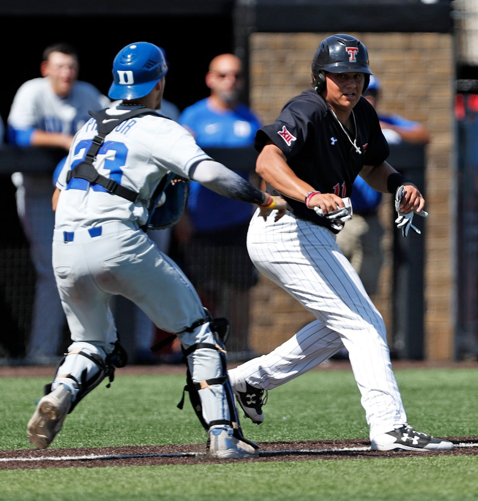 Duke's Chris Proctor (23) tags out Texas Tech's Cameron Warren (11) while trying to reach home plate during an NCAA college baseball tournament super regional game Monday, June 11, 2018, in Lubbock, Texas. [Brad Tollefson/A-J Media]
