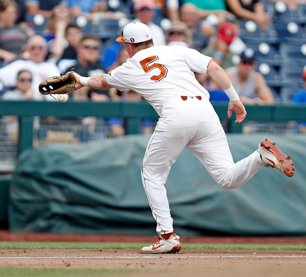 Texas' Ryan Reynolds (5) tries to catch a foul ball during a College World Series baseball game against Florida, Tuesday, June 19, 2018, at TD Ameritrade Park in Omaha, Neb. [Brad Tollefson/A-J Media]