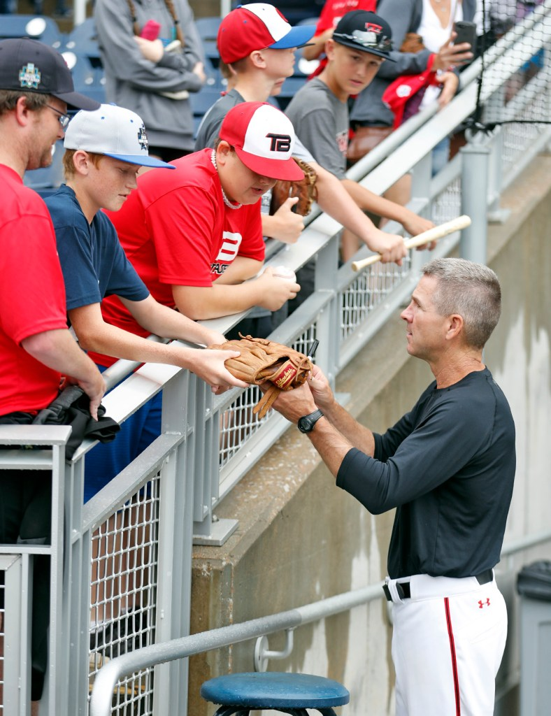 Texas Tech coach Tim Tadlock hands a signed glove back to Zac Phillips, from Lubbock, before a College World Series baseball game against Arkansas, Wednesday, June 20, 2018, at TD Ameritrade Park in Omaha, Neb. [Brad Tollefson/A-J Media]
