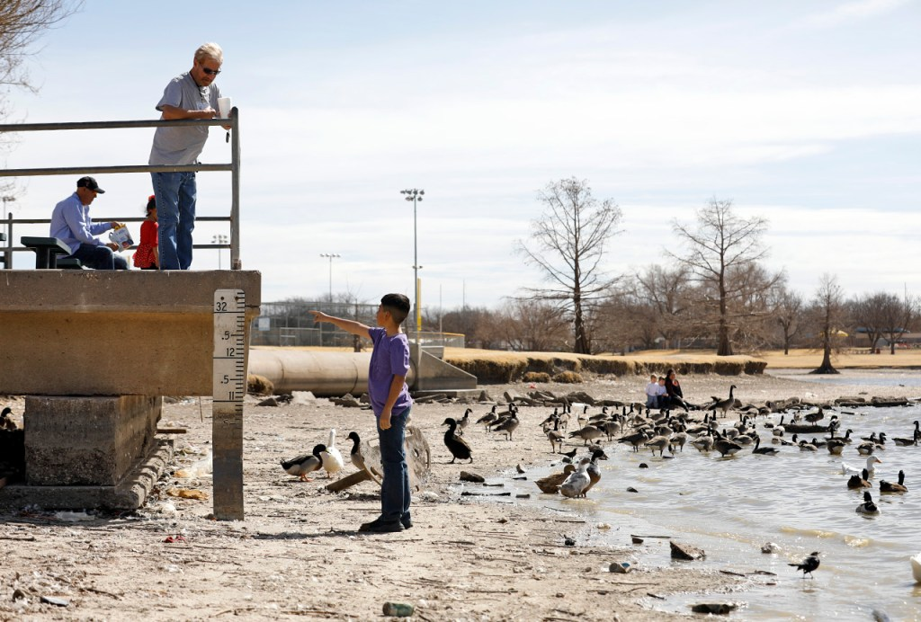 Rivera Gilbert, left, and Gabriel Romero, right, look at the geese and low water levels Wednesday, Feb. 14, 2018, at Maxey Park in Lubbock, Texas. Lubbock hasn't received any rain in 98 days. [Brad Tollefson/A-J Media]