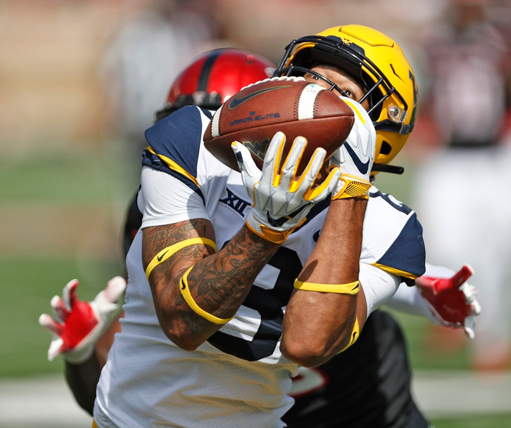 West Virginia's Marcus Simms (8) catches the ball for a touchdown around Texas Tech's Demarcus Fields (23) during the first half of an NCAA college football game Saturday, Sept. 29, 2018, in Lubbock, Texas. (AP Photo/Brad Tollefson)