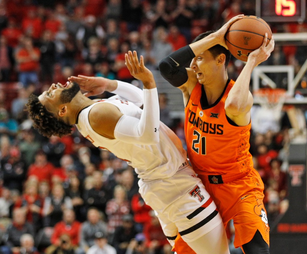 Texas Tech's Brandone Francis (1) falls down after being hit on the chin by Oklahoma State's Lindy Waters (1) during the second half of an NCAA college basketball game Tuesday, Jan. 23, 2018, in Lubbock, Texas. (AP Photo/Brad Tollefson)