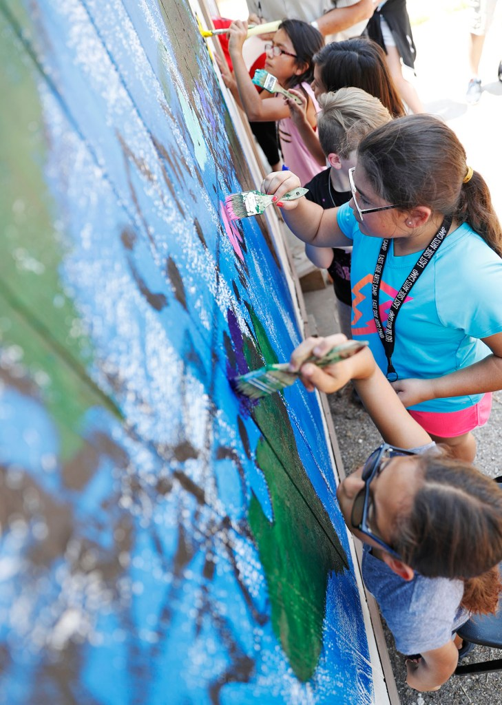 A group of kids paint a mural with the East Side Arts Camp, Thursday, Aug. 2, 2018, at Roots Community Revitalization Center in Lubbock, Texas. [Brad Tollefson/A-J Media]