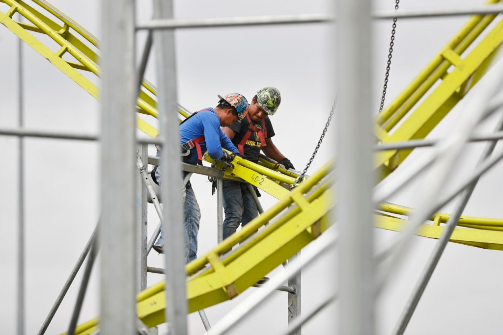 Workers install the track on a roller coaster ride before the fair opens, Wednesday, Sept. 19, 2018, at Panhandle South Plains Fair in Lubbock, Texas. [Brad Tollefson/A-J Media]