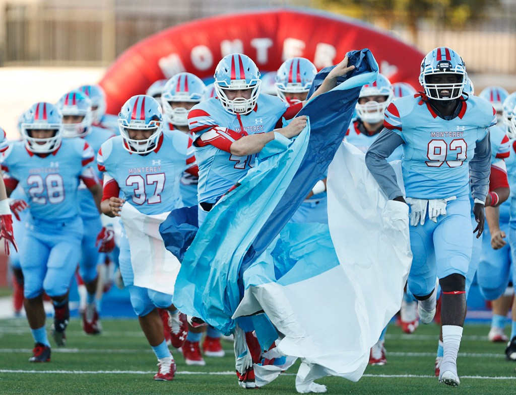 Monterey's Randy Antu (40) gets caught up in the paper banner when running onto the field before the game against Abilene Cooper, Thursday, Sept. 27, 2018, at PlainsCapital Park-Lowrey Field in Lubbock, Texas. [Brad Tollefson/A-J Media]