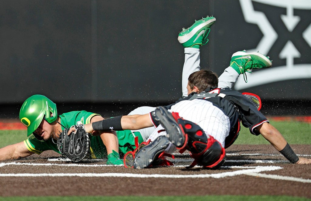 Oregon's Aaron Zavala (13) slides into home plate to score around Texas Tech's Cole Stilwell (18) during the game Friday, Feb. 15, 2019, at Dan Law Field at Rip Griffin Park in Lubbock, Texas. [Brad Tollefson/A-J Media]