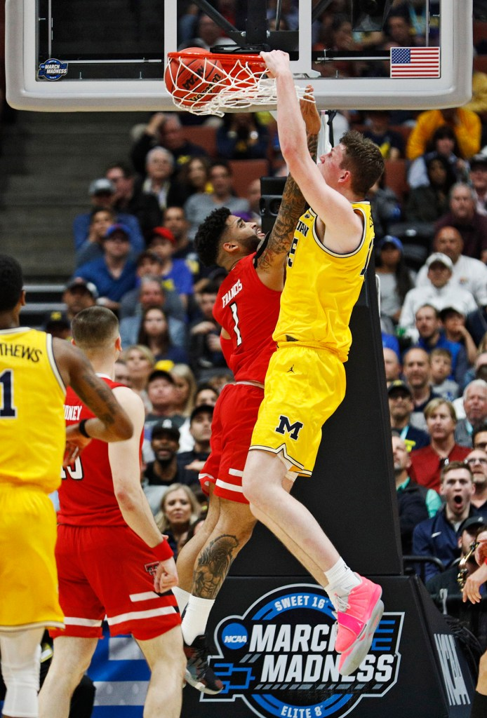 Michigan's Ignas Brazdeikis (13) dunks the ball over Texas Tech's Brandone Francis (1) during the NCAA tournament Sweet 16 game Thursday, March 28, 2019, at Honda Center in Anaheim, Calif. [Brad Tollefson/A-J Media]