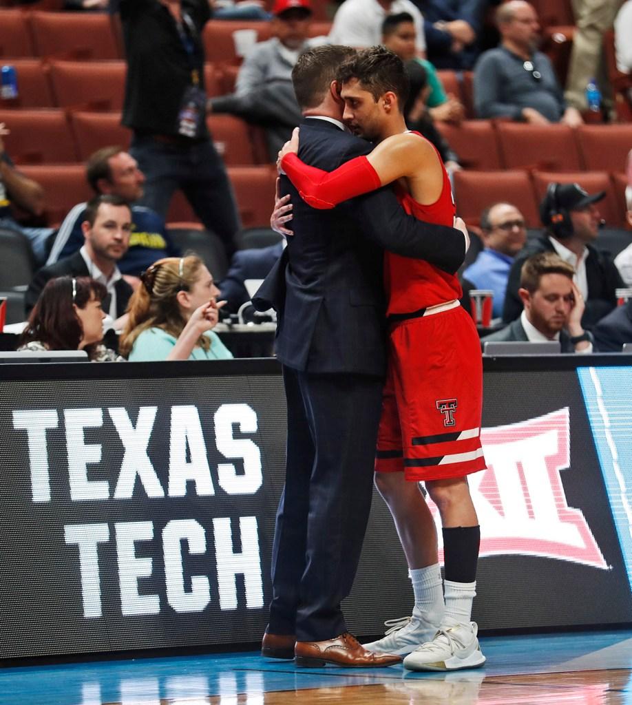 Texas Tech coach Chris Beard hugs Davide Moretti (25) as he walks off the court during the NCAA tournament Sweet 16 game against Michigan Thursday, March 28, 2019, at Honda Center in Anaheim, Calif. [Brad Tollefson/A-J Media]