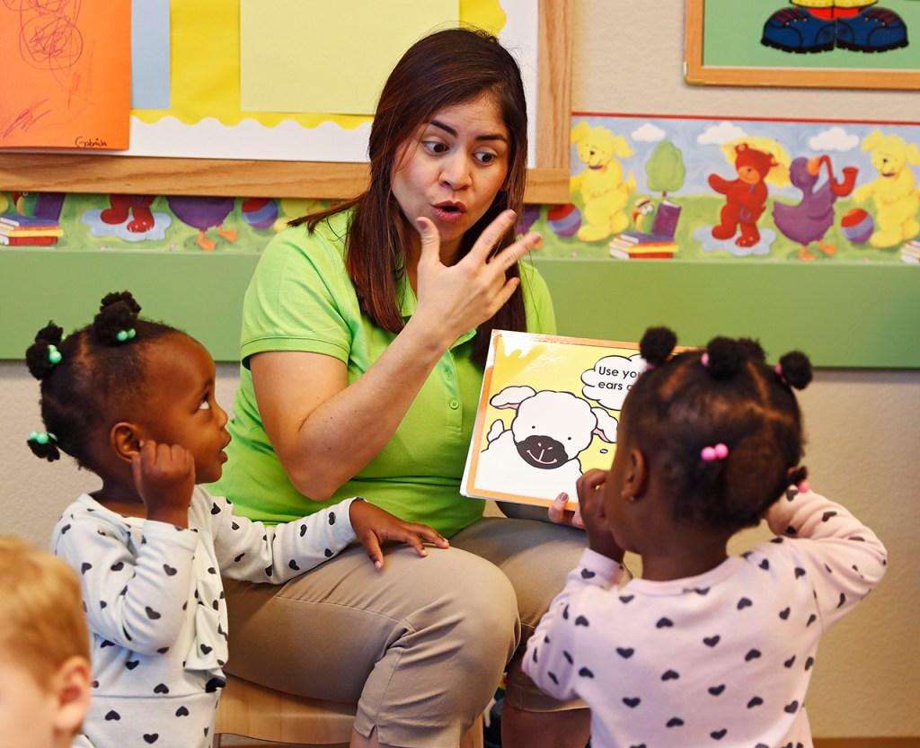 Euraliz Mavarez reads a book to Gabriella Palmer-Ikuku and Izabella Palmer-Ikuku during reading time at Primrose School of Midland at Westridge on Tuesday, April 23, 2019 in Midland, Texas. (Brad Tollefson/AP Images for Primrose Schools)