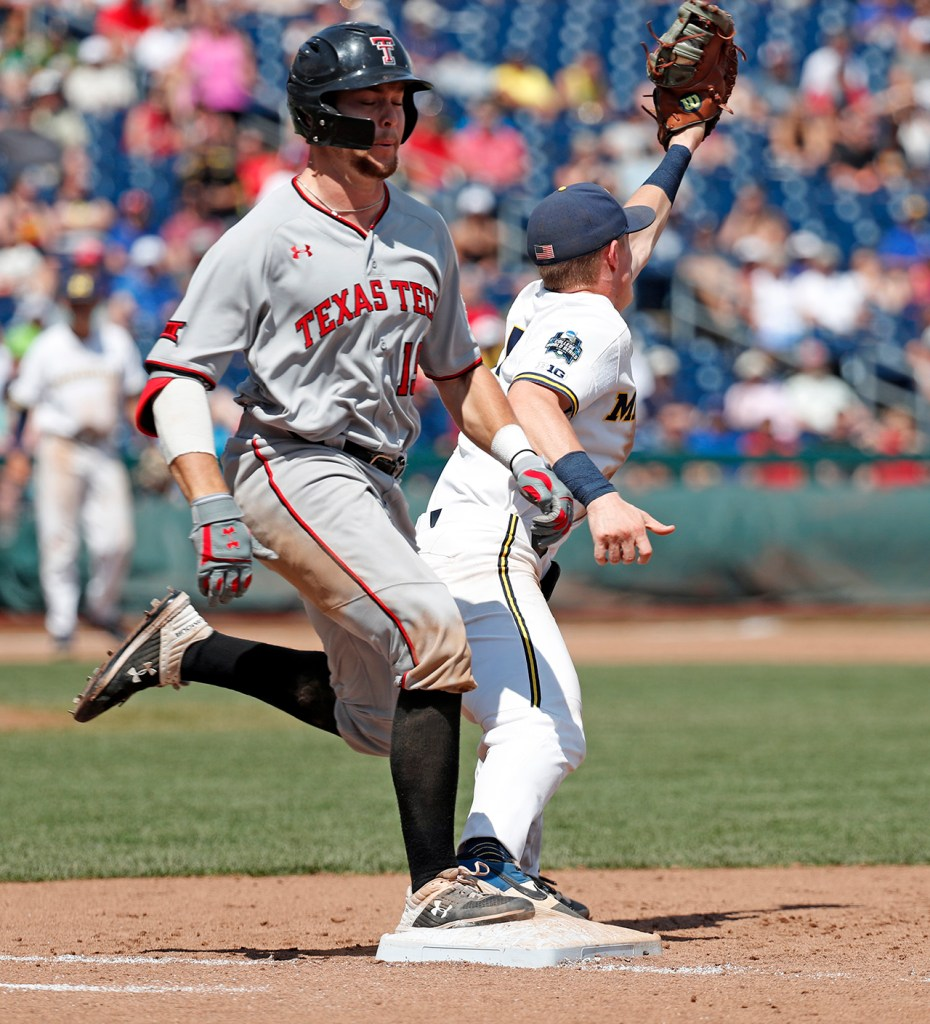 Texas Tech's Easton Murrell (19) reaches first base past Michigan's Jimmy Kerr (15) during the College World Series game against Michigan, Friday, June 21, 2019, at TD Ameritrade Park in Omaha, Neb. [Brad Tollefson/A-J Media]
