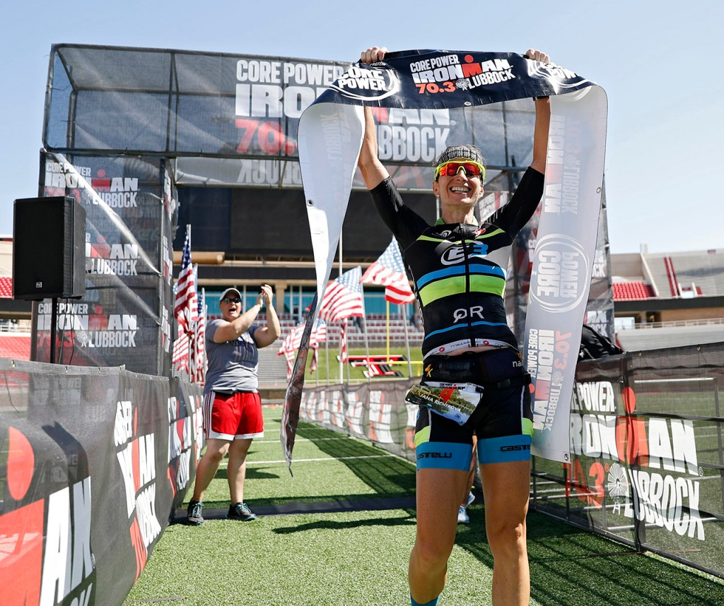 Jana Richtrova, from Spring, holds up the banner after crossing the finish line during the Ironman 70.3 Lubbock, Sunday, June 30, 2019, at Texas Tech in Lubbock, Texas. [Brad Tollefson/A-J Media]