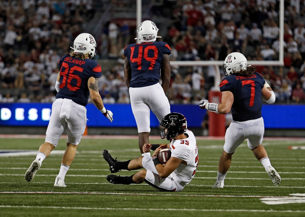 Arizona's Justin Belknap (86), Jalen Harris (49) and Colin Schooler (7) celebrate after tackling Texas Tech's Mark Richardson (35) on a fake punt during the game Saturday, Sept. 14, 2019, at Arizona Stadium in Tucson, Ariz. [Brad Tollefson/A-J Media]