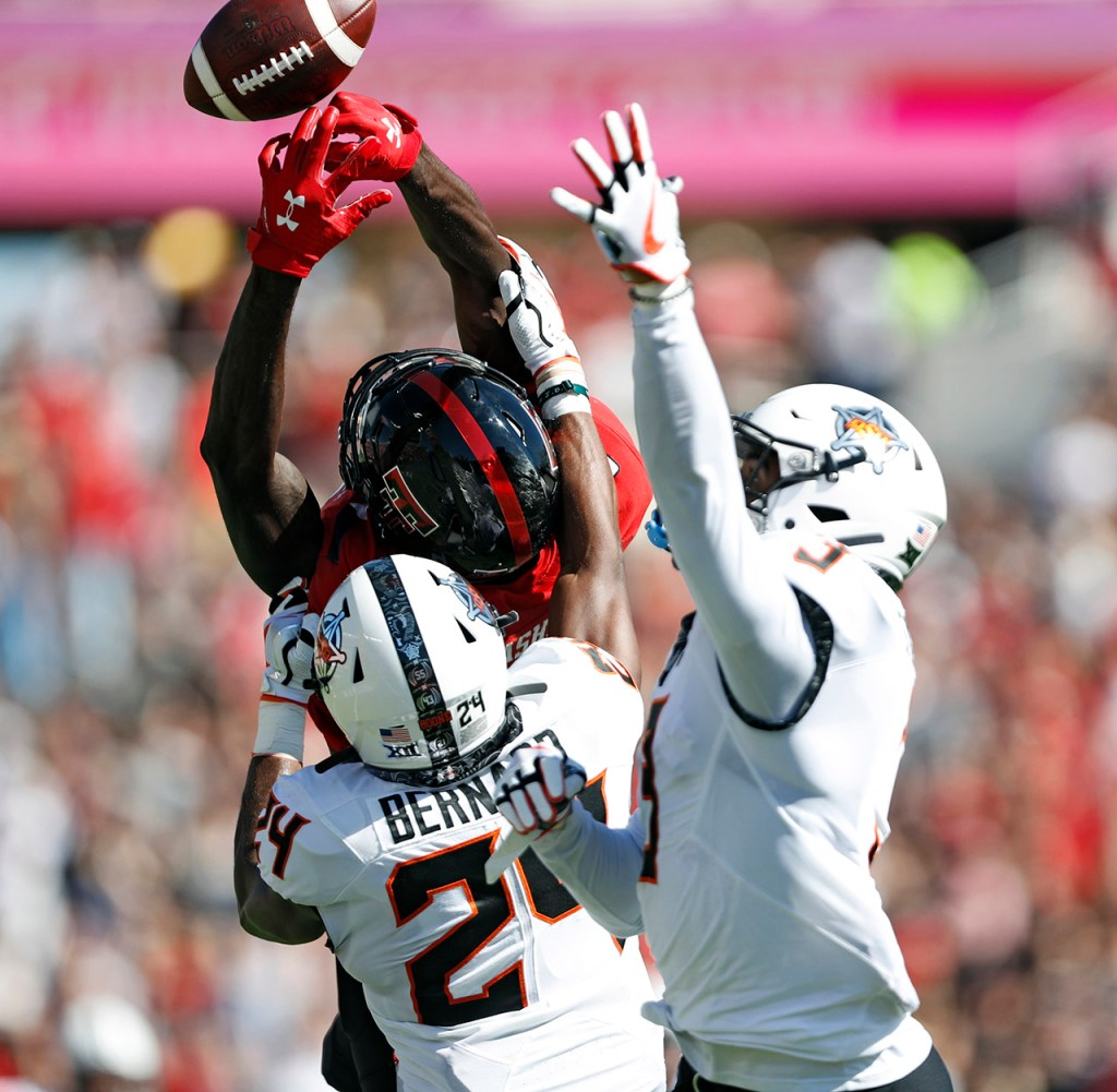 Oklahoma State's Jarrick Bernard (24) and Tre Sterling (3) break up a pass intended for Texas Tech's T.J. Vasher (9) during the game Saturday, Oct. 5, 2019, in Lubbock, Texas. (AP Photo/Brad Tollefson)