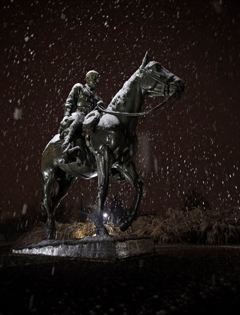 Snow falls around the statue of Will Rogers and Soapsuds during a snowstorm Friday, Jan. 8, 2016, in Lubbock, Texas. [Brad Tollefson/Lubbock Avalanche-Journal]