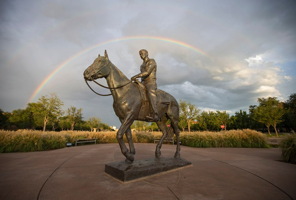 A rainbow stretches across the sky behind the statue of Will Rogers and Soapsuds, Wednesday, Aug. 24, 2016, in Lubbock, Texas. [Brad Tollefson/Lubbock Avalanche-Journal]