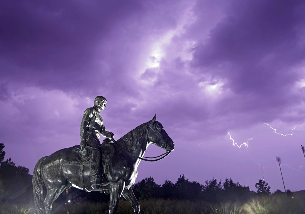 Lightning flashes in the sky behind the statue of Will Rogers and Soapsuds, Sunday, Sept. 29, 2019, in Lubbock, Texas. [Brad Tollefson/Lubbock Avalanche-Journal]