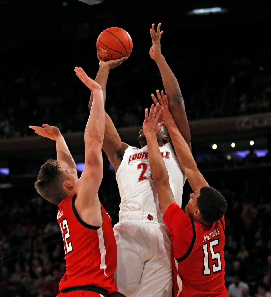 Louisville's Steven Enoch (23) shoots the ball over Texas Tech's Andrei Savrasov (12) and Kevin McCullar (15) during the first half of the Jimmy V Classic game Tuesday, Dec. 10, 2019, at Madison Square Garden in New York, N.Y. [Brad Tollefson/A-J Media]