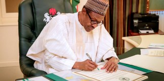 buhari signing a document