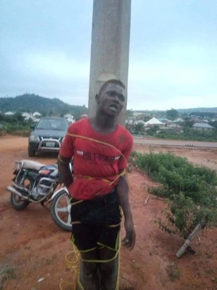 See Photos As Suspected Thief Caught And Tied To Electric Pole For Stealing Generator In Abuja