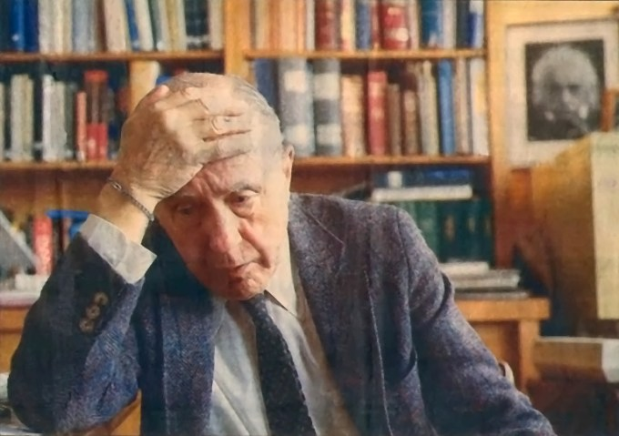 John Archibald Wheeler in 1987, with Einstein's portrait hanging prominently in  his office. By the time of his death, Wheeler was last living link to Einstein and Niels Bohr, with both of whom he had collaborated directly.