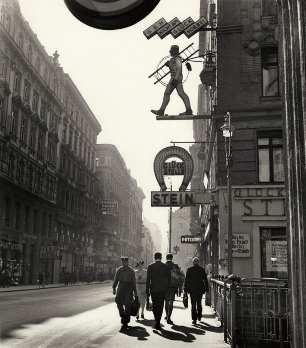 """Vienna in the 1930s. The sign, belonging to a gambling parlor, reads: """"Don't let luck pass you by."""" A horseshoe and chimney sweep, superstitious symbols of good fortune, appear above. (Photograph:  Roman Vishniac)"""