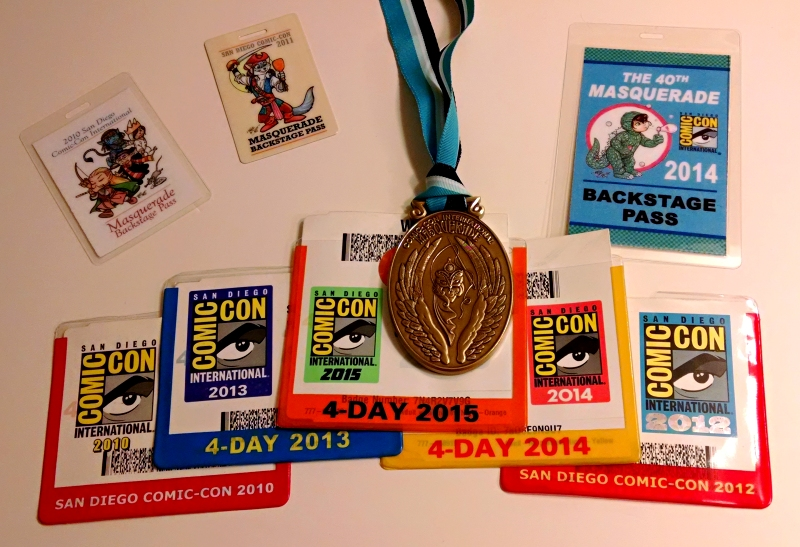 [image: a selection of comic-con badges and a masquerade medal]