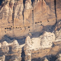 Ancient man-made caves are littered over the cliff faces.