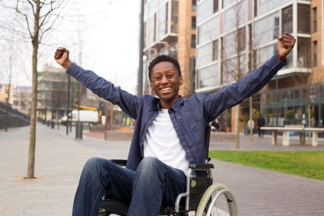 Young man in a wheelchair celebrating finding his home