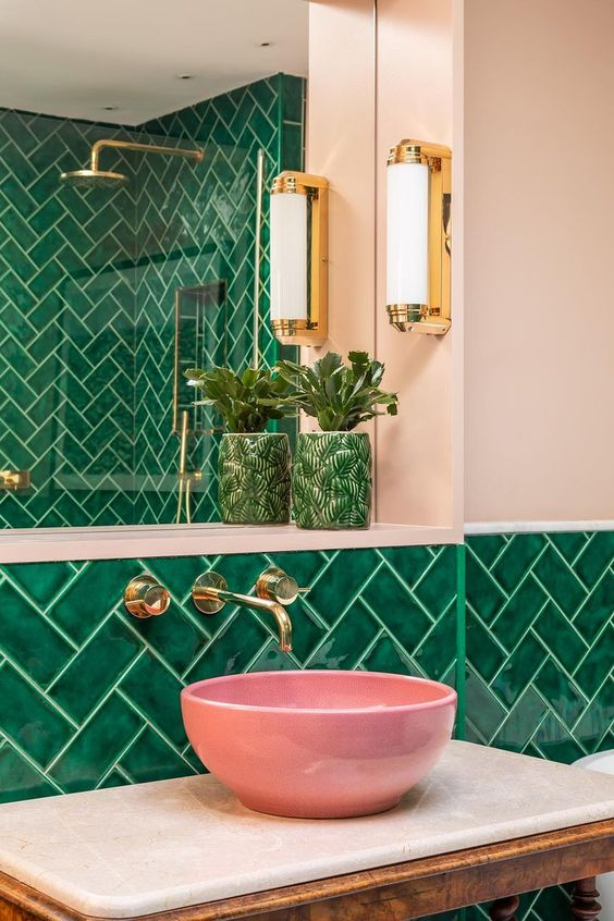 Pink walls with green bathroom tiles and pink marble sink