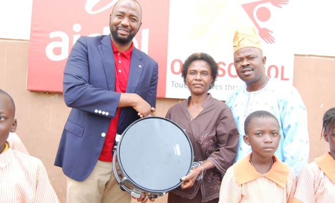 Human Resources Director, Airtel Nigeria, Jubril Saba handing over a set of drums donated by Airtel Nigeria to the Head Teacher, Oremeji Primary School 2, Adunni Risikatu Animashaun, and the Education Secretary, Ajeromi-Ifelodun Local Government Education Authority, Adeogun Adio Adewale in Ajegunle, Lagos