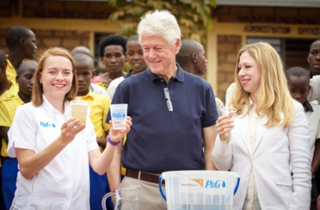 President Bill Clinton and daughter, Chelsea join P&G's Allison Tummon Kamphuis in purifying water using P&G water purification packets in Rwanda