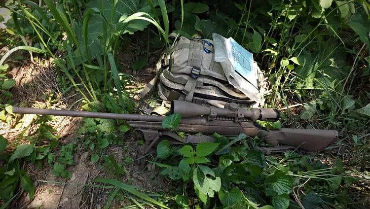 Ruger American Predator firing position on backpack with rifle data book.