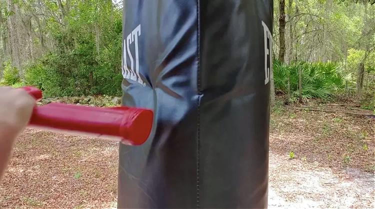 ASP red training gun buttsroke against punching bag to test for durability.