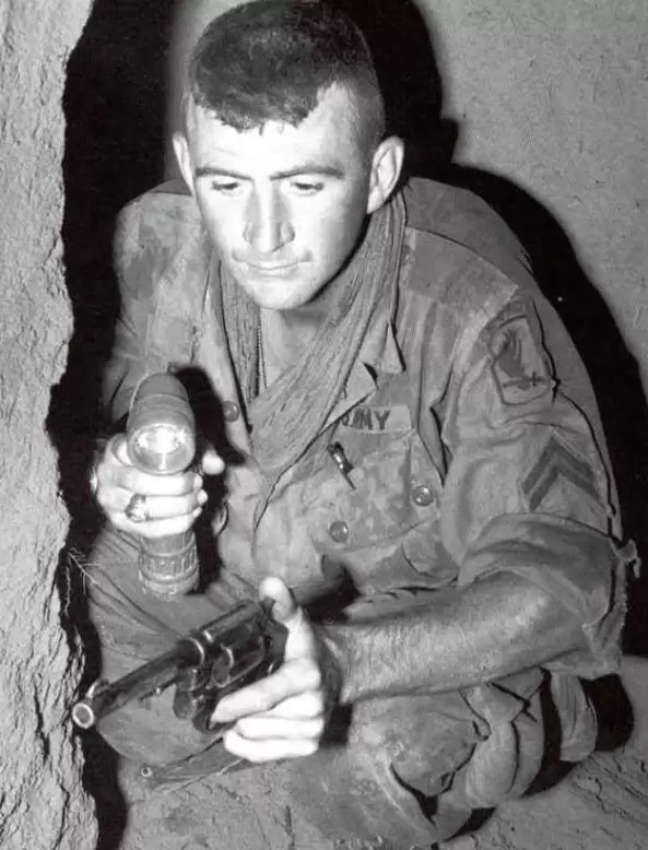 """A """"tunnel rat"""" (unknown identity) in Vietnam with flashlight and revolver."""