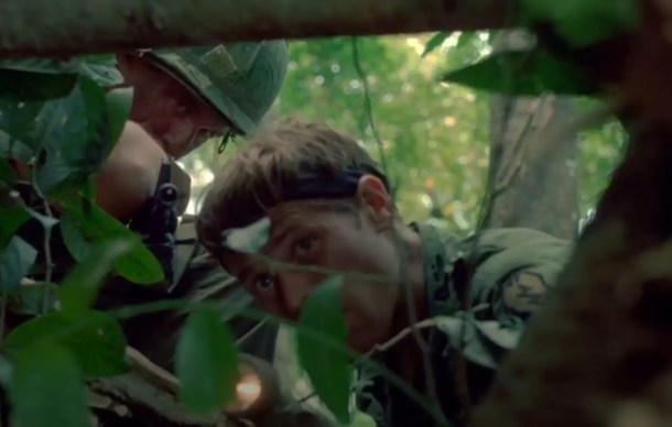 Willem Dafoe, playing Sgt. Elias, prepares to enter the tunnels beneath a bunker complex in the movie Platoon. He carries a 1911 pistol in one hand and an angle head military flashlight in the other.