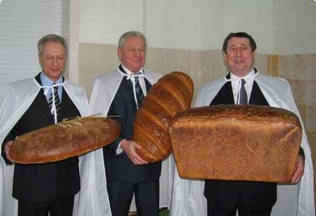 3 guys holding 3 oversized bread