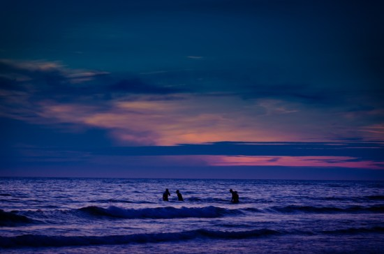 Second image showing a silhouette of swimmers in the sea at sunset taken at Widemouth Bay Cornwall, UK on June 24, 2014.