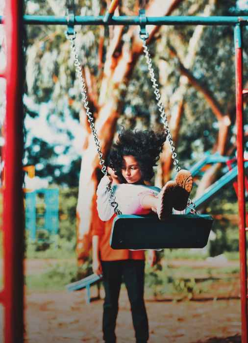 girl in a swing at the park
