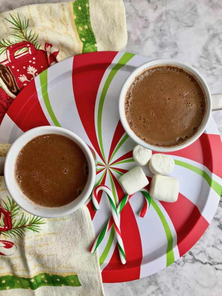 Two mugs of cinnamon oat milk hot chocolate with marshmallows and candy canes.