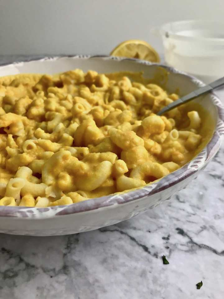 Close up of vegan mac and cheese with lemon and coconut milk in the background.