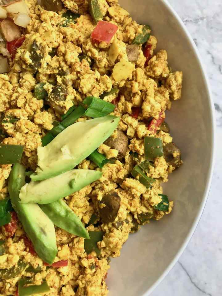 Close up of half a bowl of vegan tofu scramble, topped with avocado slices.