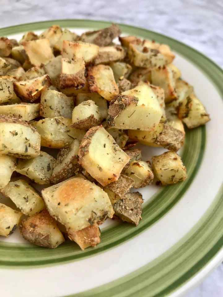 Close up of diced roasted potatoes on a white and green plate.