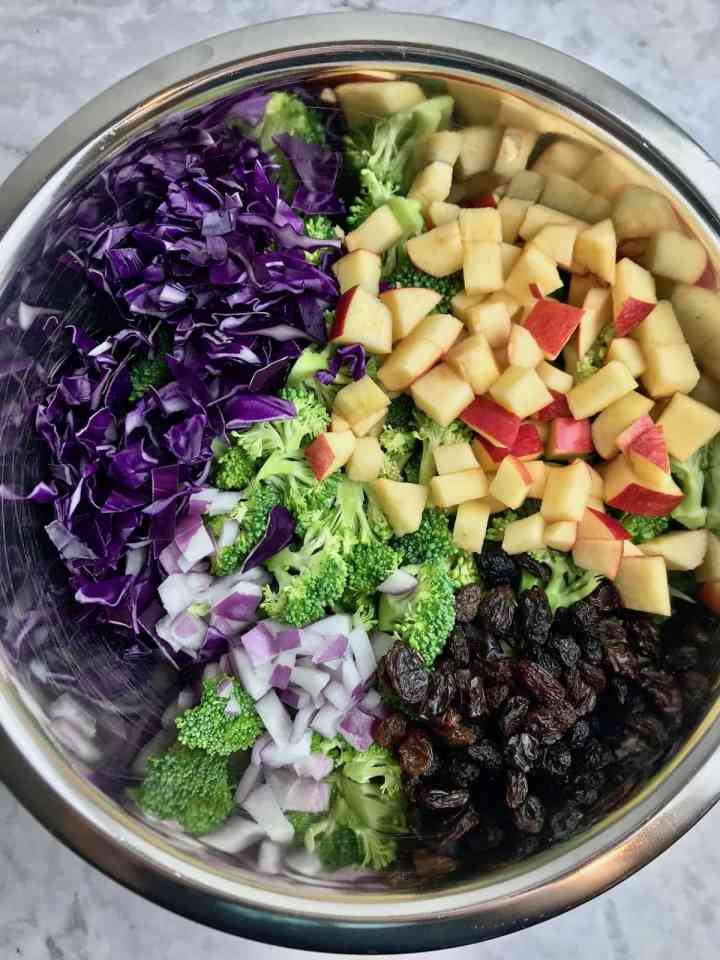 Bowl of ingredients, including chopped red cabbage, chopped apple, chopped red onion, raisins, and broccoli florets.