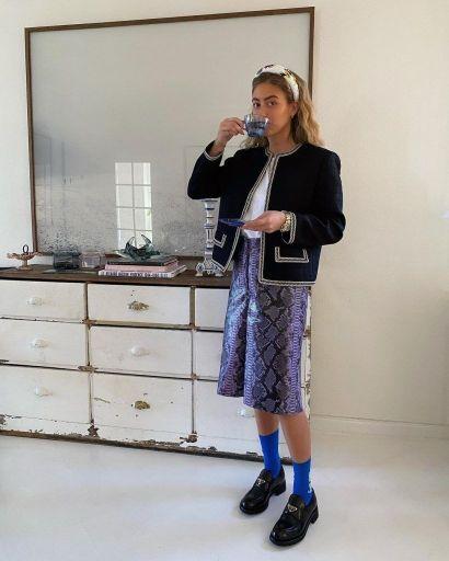 喝著茶的女士服裝為黑色無領西裝外套搭配藍紫色動物紋五分褲,鞋款則以黑色樂福鞋搭配靛藍色長襪