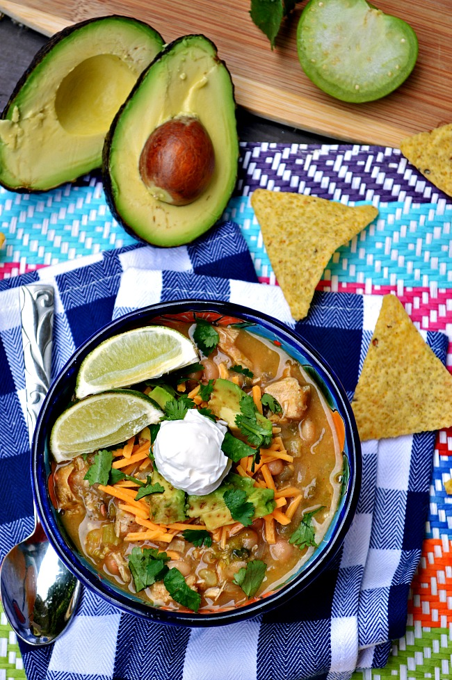 Keep your figure happy and your tummy satisfied with this healthy and filling Gluten Free White Bean Chicken Chili. Load it up with toppings for a meal in one bowl.