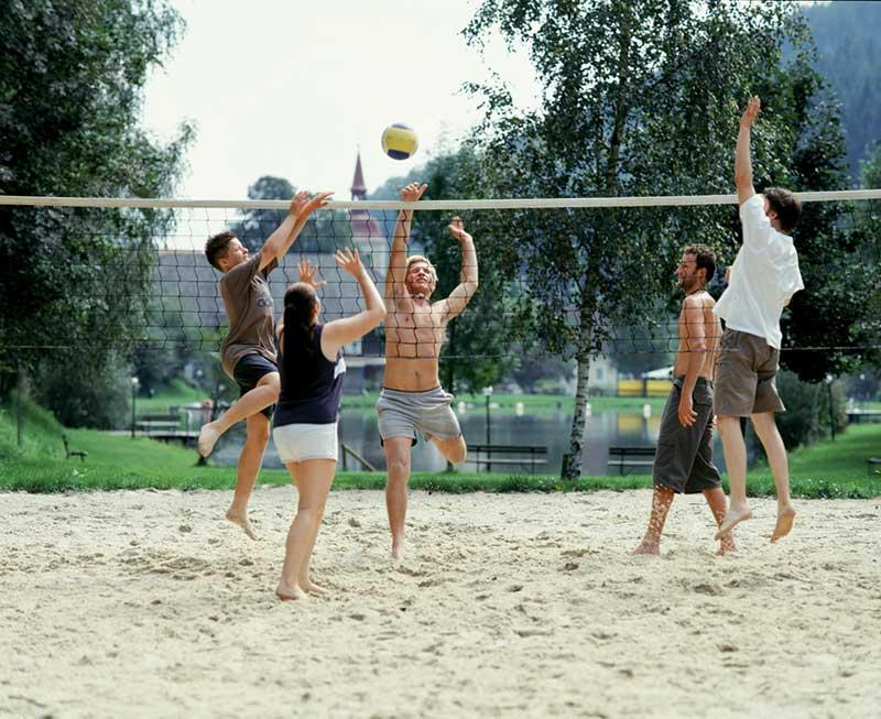 Junge Leute spielen Volleyball auf einem Beachvolleyballplatz
